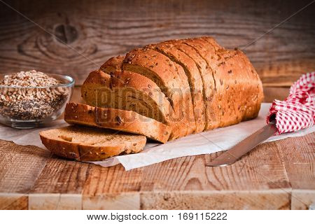 Whole wheat bread with seeds on baking paper.