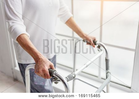 Old woman holding foldable walker while situating near window in hospital. Close up of her arms