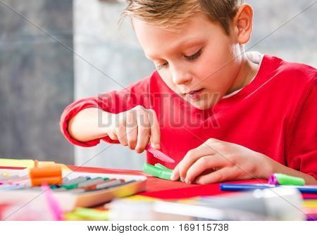 Concentrated schoolchild cutting green plasticine at school