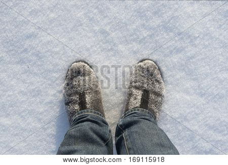 Frozen felt boots on the snow background