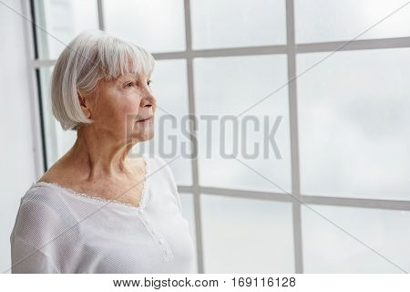 Waist up portrait of dreaming old woman watching at window in hospital room