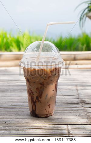 Iced coco or chocolate with straw in plastic cup on wood background