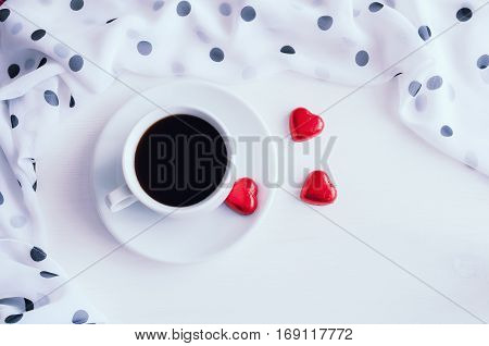 Romantic background - cup of coffee heart shaped candies with frame of chiffon polka dot scarf. Romantic still life with romantic mood. Romantic background