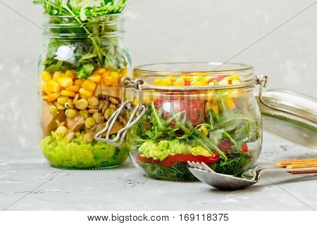 Healthy take-away lunch jars. Guacamole corn tofu beans arugula. Paprika falafel dill and corn. Clean eating vegetarian raw detox dieting concept