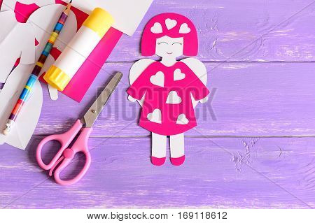 Cute angel crafts from paper, scissors, glue stick, cardboard sheets, paper templates on purple wooden background with empty place for text. Simple kids crafts for Valentine's day. Top view