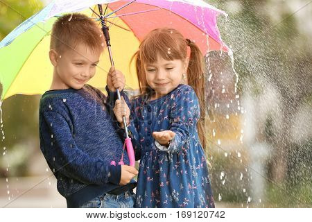 Portrait of cute children with umbrella in rain