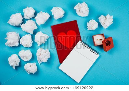 Valentines card and many crumpled sheets of paper on blue background. Letter with a proposal get married. Flat lay style.