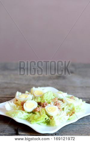Homemade cabbage salad with tuna and quail eggs on a plate and vintage wooden table. Salad made with fresh napa cabbage, canned tuna and hard-boiled quail eggs. Vertical photo
