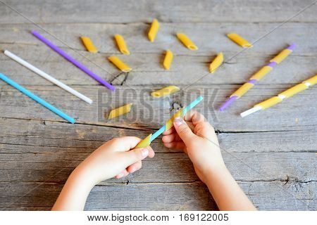 Small kid holds straw and dried tube pasta in his hands. Kid stringing pasta onto straw. Interesting and simple game for kids to develop fine motor skills. Wooden background