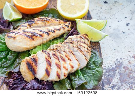 Grilled chicken breast in citrus marinade on salad leaves and wooden cutting board horizontal copy space