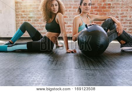 Portrait of two young women sitting on gym floor with medicine ball. Mixed race females in healthclub.
