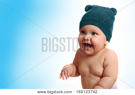 Baby in the hat smiling while sitting in bed