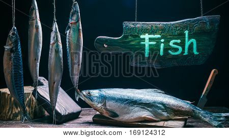 Old-fashioned fish store. Wooden counter with salmon and mackerels. Green lighting on wood sign