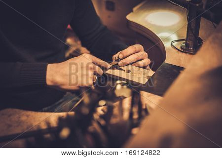 Jeweler at work in jewelery workshop.