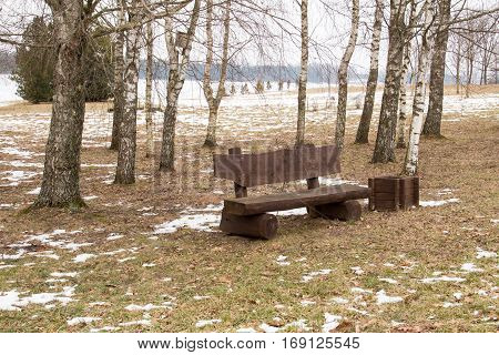Lonely wooden bench in a park at winter time