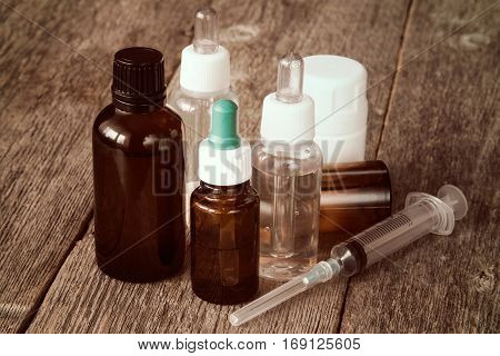 Pharmacy theme. Syringe and various medicaments on the wooden background