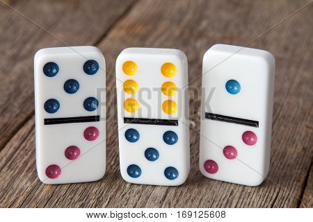 Three dominoes standing on a wooden background