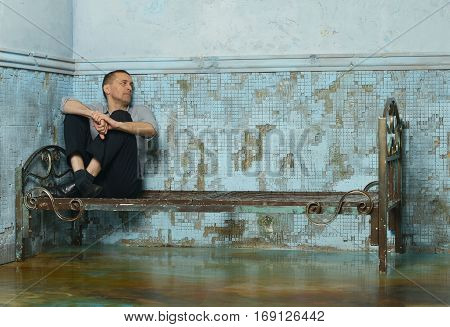 Man on the metal rusty bed in prison