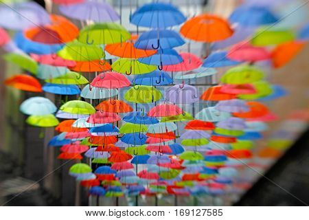 Bright colorful umbrellas as street decoration hanging up in the open air.