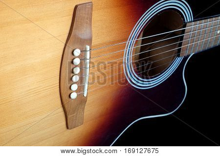 Classic acoustic six strings guitar sunburst color top from spruce with cutaway fragment isolated on black background side view closeup