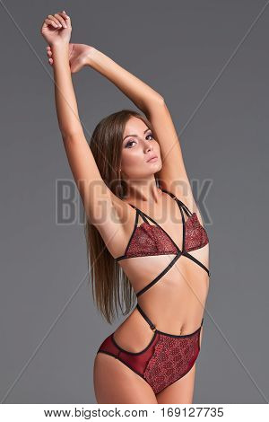 Beautiful young woman in a sexy lingerie on a gray background. Model standing and looking at the camera