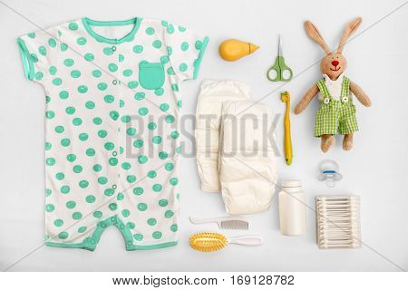 Baby care accessories and clothing on light background, top view