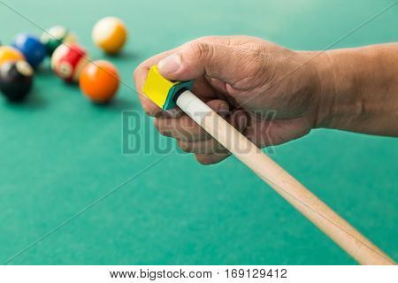 Hand Applying Chalk On Tip Of Billards Pool Stick