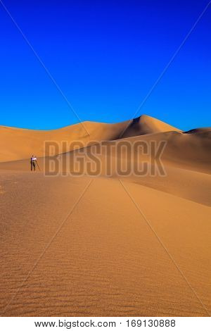 Woman - photographer in a striped T-shirt is ready to shoot with a tripod among the sand dunes. Sunrise in the orange sands of the desert Mesquite Flat, USA