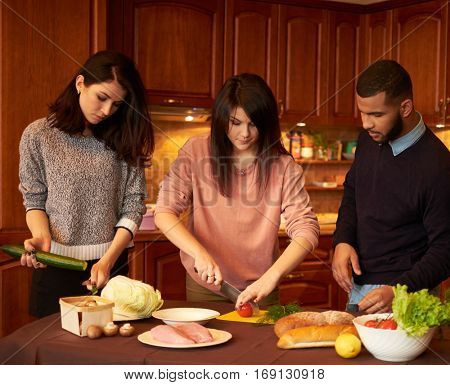 Group of multi ethnic young friends in kitchen prepare for party.