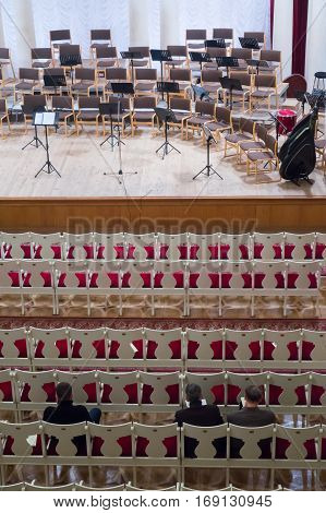 Empty auditorium and the stage before the concert. On the stage music stands with notes, bandura and drum. In the hall three men