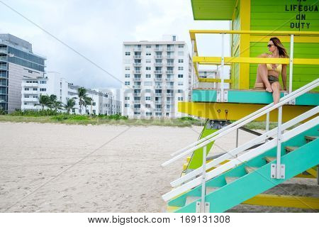 Beautiful woman in bikini sitting at the lifeguard station, Miami