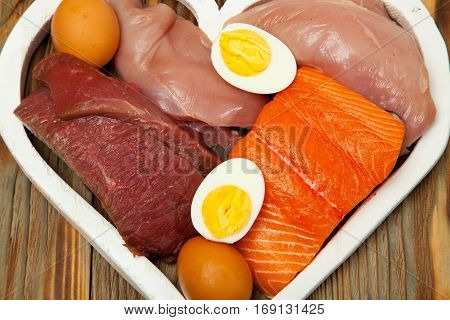 Proteins, Fish, Cheese, Eggs, Meat, Chicken In A Heart On  Wooden Background