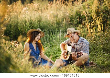 Young couple of brunette girlfriend and boyfriend sitting on grass at meadow smiling and having fun together wearing in hats. Looking each other and singing. Man playing on guitar. Sunny summer day.