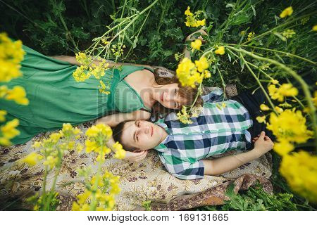 View from above of young couple of boyfriend and girlfriend lying on grass among yellow flowers in meadow. Woman in green dress and man in checked shirt embracing and looking at camera. Summertime.