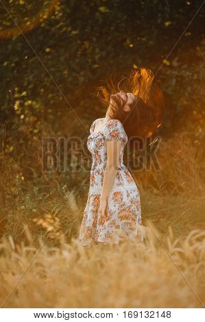 Portrait of beautiful brunette woman with long hair standing among grass in meadow in summer season. Pretty girl wearing dress in floral print playing with her hair raises his head up