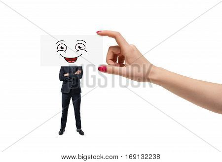Big woman's hand is putting a smiley face on white cartoon on an employee's head isolated on white background. Leadership. Business relations. Management