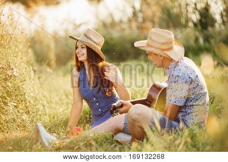 Couple of brunette girlfriend and boyfriend sitting on grass at meadow smiling and having fun together wearing in hats. Man singing and playing on guitar. Woman looking away. Romantic atmosphere.