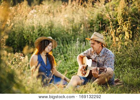 Happy couple of brunette girlfriend and boyfriend sitting on grass at meadow smiling and having fun together wearing in hats. Looking each other and singing. Man playing on guitar. Sunny day.