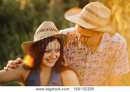 Portrait of couple of girlfriend and boyfriend in hats sitting on grounds in meadow having fun smiling and touching each other. Brunette woman with long hair wearing dress and man in printed shirt.
