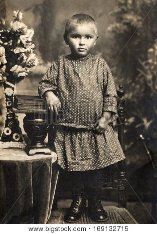 1914 photograph of little girl in sepia-toned desaturated color file.
