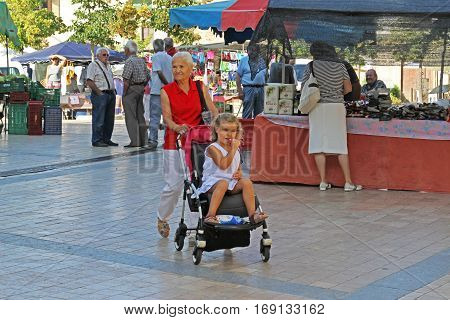 Besalu Spain - September 09 2014: Grandmother walking with baby girl in street of Besalu in Spain
