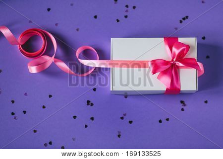 White present box with pink bow on purple background. Valentine's day, 8 march and birthday concept. Flat lay style.