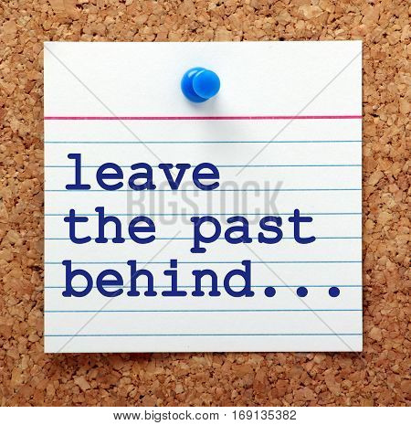 The words Leave The Past Behind on a note card pinned to a notice board as a reminder to be optimistic and look forward to the future