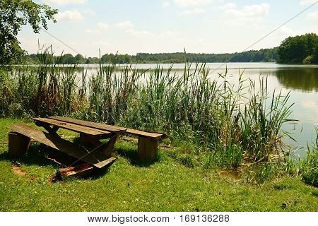 Holidaymaker wooden table with a broken bench near the pond.