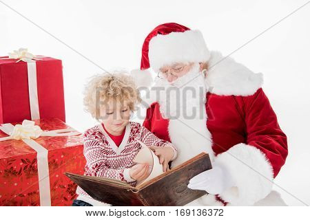 Santa Claus and kid sitting and reading a book together near gift boxes
