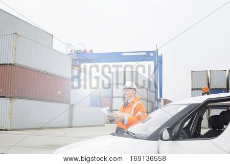 Middle-aged man talking on walkie-talkie while using laptop in shipping yard