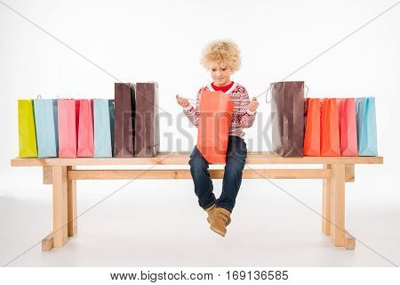 Kid sitting on bench with shopping bags and looking into one of them isolated on white