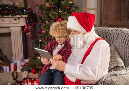 Santa Claus sitting on armchair with kid on knee and using digital tablet