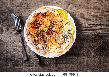 Herb omelette with cheese in white plate on wooden table