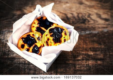 Pasteis de Nata - creamy egg tart with sweet curstard black crust and sugar powder on wooden background. Pasteis de Belem pastry